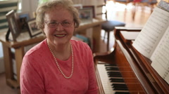 A static shot of a happy elderly woman sitting on a piano bench next to a piano. - stock footage