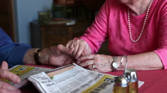 A shot of an elderly couple talking with one another at a table with a newspaper Stock Footage
