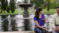 A shot of a young couple conversing with each other in front of a water Stock Footage