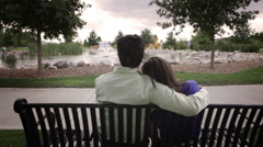 Stock Video Footage of A tracking shot of the back of a couple sitting on a bench gazing off into the