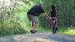 Thrilled Dad Helps Daughter Ride Bike Down Forest Path Stock Footage