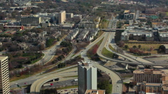 A static, wide shot of cars flowing on the freeway under bridges with buildings Stock Footage