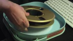 VIDEOTAPE REEL BEING REMOVED FROM BOX - stock footage