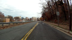 Driving down a road in Washington DC. Trees and buildings line each side of the - stock footage
