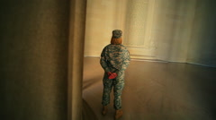 A static shot of the back of a female soldier who is gazing at the constitution. Stock Footage
