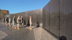 A static shot of a soldier looking up at a wall of names of deceased soldiers in Stock Footage