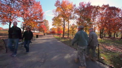 Stock Video Footage of A handheld shot of a group of soldiers walking down a path in a park in