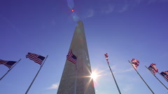 A static shot w/ lens flare of seven flags waving in the wind in front of the Stock Footage