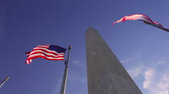 A static shot of two american flags waving in the wind in front of the Stock Footage