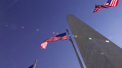A tracking shot looking up at the Washington Monument on a windy day in Stock Footage