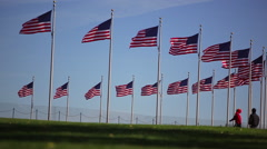 A static shot of three people running by a circle of flags in Washington DC. Stock Footage