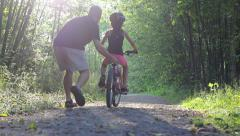Excited Dad Helping Daughter Ride Bike Down Forest Path Stock Footage