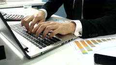 Business people typing on a laptop computer in the office - stock footage