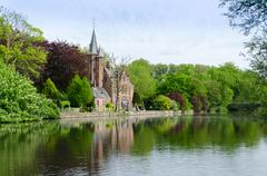 Flemish style building reflecting in Minnewater lake - stock photo