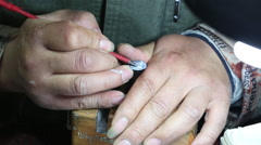 Up close view of persons hands as they carve into a metal post. - stock footage