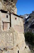 Cells of Geghard rock monastery with ancient khachkars,crosses,Armenia - stock photo