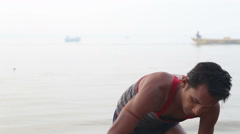 Man scrubbing clothes on a stone at shore of Ganges river. - stock footage