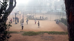 Foggy view of young men playing basketball on a dirt court. Stock Footage