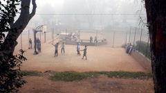 Foggy view of young men playing basketball on a dirt court. - stock footage
