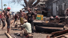 Panning shot of men working in a rundown village. Stock Footage