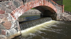 Retro red brick and stone arch and waterfall water flowing. 4K Stock Footage