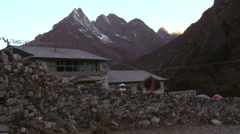 Stock Video Footage of Stone wall and buildings in the shadow of Himalayan peaks.