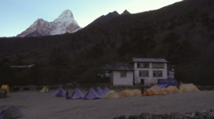 Man walking among tents below Ama Dablam in Nepal. Stock Footage