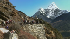 Hikers and sherpas carrying gear up a trail in the Himalayas. - stock footage