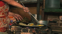 Nepali woman cooking food on a frying pan. Stock Footage