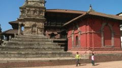 Young Nepali children walking past an old temple. Stock Footage