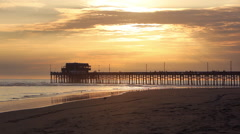 Static view of the Newport Pier as people walk and play on the beach at Sunset. - stock footage