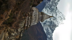 Vertical shot of Time-lapse of a buddhist stupa with Ama Dablam peak in the Stock Footage