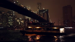 Shot at night overlooking the East River and the Brooklyn Bridge as a boat Stock Footage