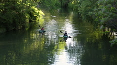 View of people paddling kayaks down the San Antonio River. - stock footage