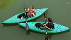 View of 2 people sitting in kayaks in the San Antonio River. - stock footage