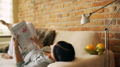 Woman lying on the sofa at home and reading magazine Stock Footage