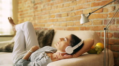 Woman chilling on the sofa and listening music Stock Footage