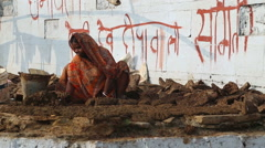 Woman kneading mud at Ganges bay, with graffiti on wall in background. Stock Footage