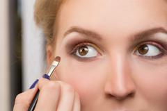 girl applied make-up on her eyes - stock photo