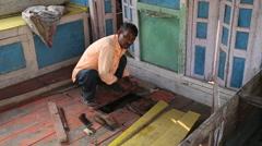 Stock Video Footage of Man scrubbing a material at floor of workshop in Varanasi.