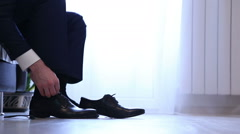 Man putting on and tying black dress shoes formal wear Stock Footage