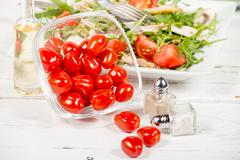 Stock Photo of Small tomatoes in a glass jar with seasonal salad