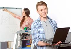 Two students with three-dimensional printer - stock photo