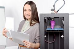 Beautiful girl with three-dimensional printer - stock photo