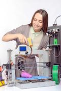 Beautiful girl with three-dimensional printer - stock photo