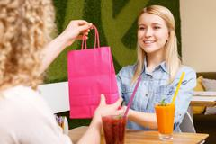 Pretty young woman getting present in cafe - stock photo