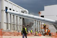 Waste plant outside process workers - stock photo