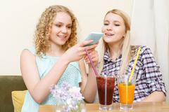 Two girls in cafe taking picture of cocktails Stock Photos