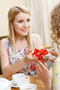Blond woman giving gift in cafe - stock photo