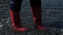 4K woman in red boots are walking in the water, very dark footage Stock Footage